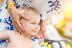 Madre che applica la crema di protezione della protezione solare sul piccolo fronte sveglio del ragazzo del bambino Mamma che usa fotografie stock libere da diritti