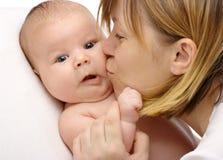 Madre che bacia il suo bambino immagine stock libera da diritti