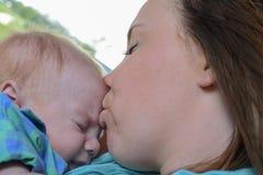 Madre che bacia il suo bambino immagini stock