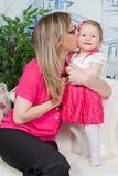 Madre che bacia la sua figlia Fotografie Stock