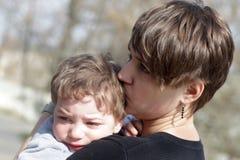 Madre che bacia suo figlio gridante Immagini Stock