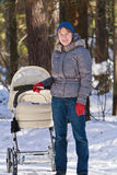 Madre che cammina con il carrello di bambino in inverno Fotografia Stock Libera da Diritti