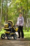 Madre che cammina con la carrozzina Immagini Stock Libere da Diritti