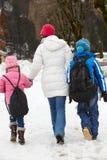 Madre che cammina due bambini al banco in neve Fotografia Stock