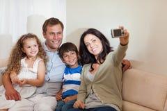 Madre che cattura la maschera della famiglia nel salone Fotografie Stock