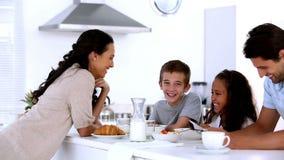 Madre che chiacchiera ai bambini alla prima colazione della famiglia stock footage