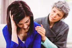 Madre che conforta figlia triste che si siede sul sofà Fotografia Stock