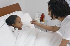 Madre che controlla la temperatura della figlia a letto immagine stock libera da diritti