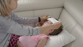 Madre che controlla temperatura di suo figlio malato Bambino malato con febbre e la malattia a letto archivi video