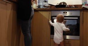 Madre che cucina vicino ai suoi giochi del bambino stock footage
