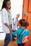 Madre che dice arrivederci ai bambini come vanno per la scuola Fotografia Stock