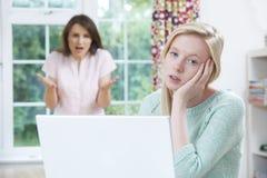 Madre che discute con la figlia adolescente sull'attività online Immagine Stock