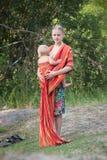 Madre che dispone figlia in imbracatura Fotografie Stock Libere da Diritti