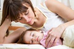 Madre che esamina bambino addormentato Immagini Stock