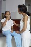 Madre che esamina la medicina bevente della figlia immagini stock