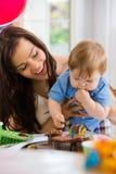 Madre che esamina neonato che mangia bigné Fotografie Stock