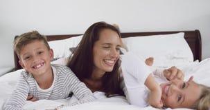 Madre che gioca con i suoi bambini in camera da letto a casa 4k stock footage