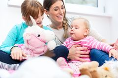 Madre che gioca con il bambino e la più grande figlia fotografia stock