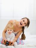 Madre che gioca con il bambino sulla sezione comandi Fotografie Stock