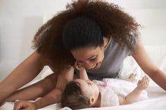Madre che gioca con la figlia del bambino in camera da letto a casa Immagini Stock Libere da Diritti