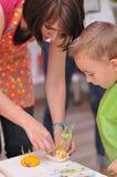 Madre che gioca con suo figlio con pasta Fotografie Stock Libere da Diritti