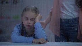 Madre che grida sulla bambina impertinente dietro la finestra piovosa, bambino di problema stock footage