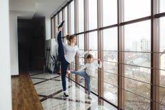 Madre che impara figlia per fare un'alta gamba allungare Fotografia Stock Libera da Diritti