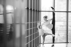 Madre che impara figlia per fare un'alta gamba allungare Fotografia Stock