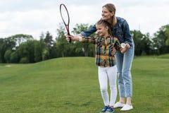 Madre che insegna alla figlia adorabile che gioca volano all'aperto Immagini Stock Libere da Diritti
