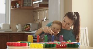 Madre che insegna a Little Boy a come contare facendo uso dei blocchi colorati e che usando i giochi educativi stock footage