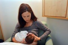 Madre che la allatta al seno neonata fotografie stock libere da diritti
