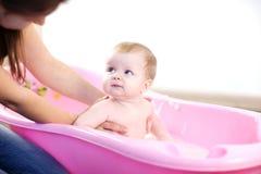 Madre che lava un bambino in vasca rosa Fotografia Stock Libera da Diritti