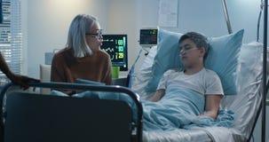 Madre che legge ad alta voce al figlio malato archivi video