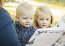 Madre che legge un libro ai suoi due bambini biondi adorabili Fotografia Stock