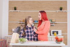Madre che mostra affetto a sua figlia mentre cucinando brunch fotografia stock
