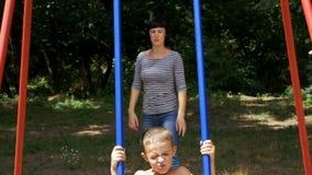 Madre che oscilla il suo ragazzo felice del bambino su un'oscillazione della via al campo da giuoco al rallentatore archivi video
