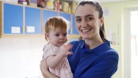 Madre che passa il figlio del bambino al lavoratore femminile della scuola materna video d archivio