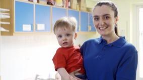 Madre che passa il figlio del bambino al lavoratore femminile della scuola materna archivi video