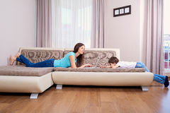 Madre che per mezzo del computer portatile su un sofà a casa Figlio con il telefono cellulare sopra Immagine Stock