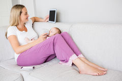 Madre che per mezzo della compressa digitale mentre alimentando il suo bambino con la bottiglia per il latte Immagini Stock Libere da Diritti