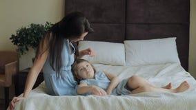 Madre che pettina i capelli della figlia sul letto a casa archivi video