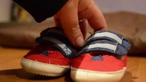 Madre che prende le scarpe di bambino dalla tavola archivi video