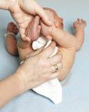 Madre che pulisce il fondo del suo bambino fotografia stock libera da diritti