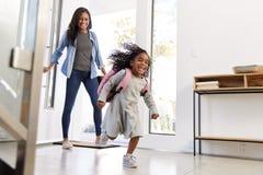 Madre che raccoglie e che porta la casa della figlia dopo la scuola immagini stock libere da diritti
