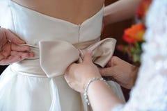 Madre che raddrizza indietro del vestito da cerimonia nuziale Immagini Stock Libere da Diritti