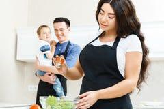 Madre che sala insalata in cucina immagini stock