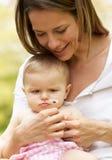 Madre che si siede con la neonata nel campo Fotografia Stock Libera da Diritti