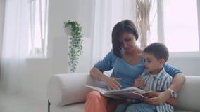 Madre che si siede con la storia della lettura del figlio all'interno video d archivio