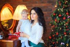 Madre che si siede vicino allo specchio che tiene una piccola figlia, sui precedenti di un albero di Natale festivo fotografie stock