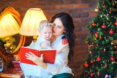 Madre che si siede vicino allo specchio che tiene una piccola figlia, sui precedenti di un albero di Natale festivo immagini stock